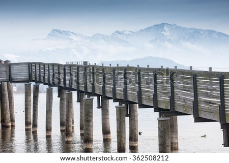 A wooden pedestrian bridge over the upper Zurich lake in the Swiss Alps - part of the old St. James Way - stock photo
