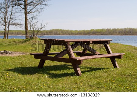 A wooden picnic table placed near a small lake