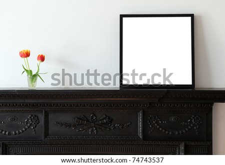 A wooden picture frame on a cast iron mantle piece.