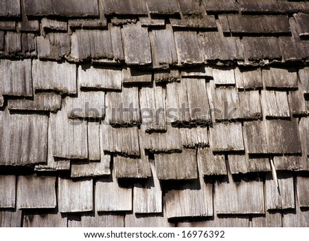A wooden roof made of ricketty differently sized wooden tiles