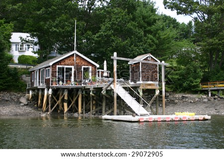 A wooden shingle dock house on an island in Maine - stock photo
