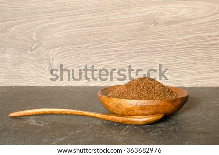 A wooden spoon and bowl with Teff, a gluten free ancient grain alternative, with late afternoon lighting  - stock photo
