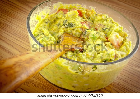 A wooden spoon in a bowl of guacamole on a wooden table