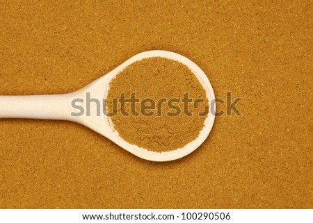 A wooden spoon on curry powder forming a background