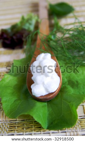A wooden spoon with fresh cottage cheese on a green lettuce leaf, arranged with dill, basil and lettuce leaves, closeup, blur background, vertical - stock photo