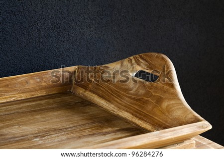 A wooden tray against a brown wall.