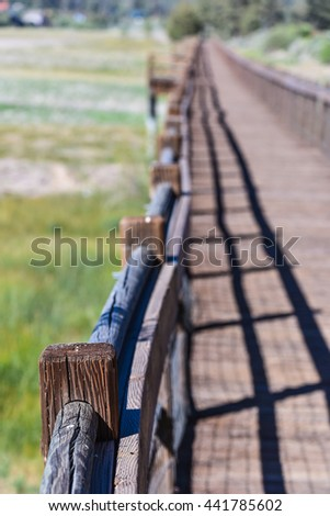 A wooden walkway bridge over Big Bear Lake with rails when the lake is 14 feet below normal - stock photo