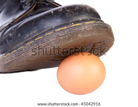 A work boot about to crush a raw egg symbolizing damage to something delicate or walking on eggshells - stock photo