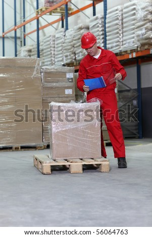 A worker checking inventory stocks at a factory storeroom. - stock photo