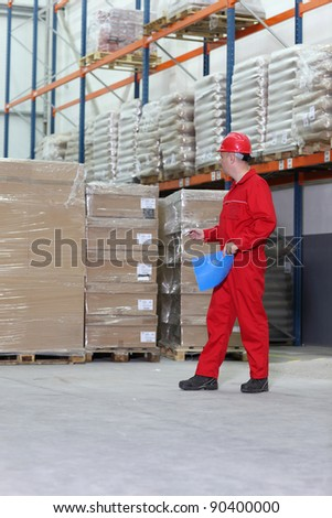 A worker checking inventory stocks at a factory storeroom