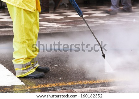 A worker cleaning the streets with water pressure - stock photo
