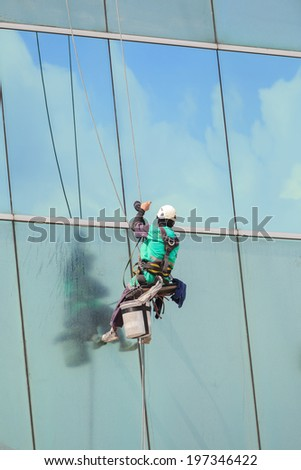 A worker cleaning windows service on high rise building - stock photo