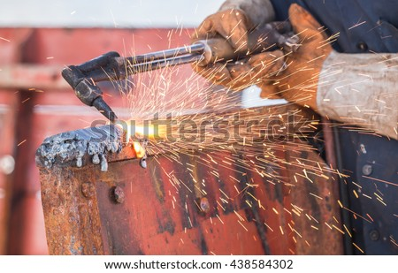 A worker cutting steel using metal torch