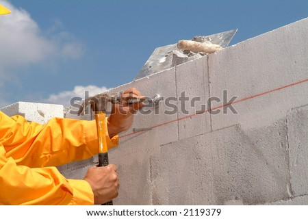 a worker hand nailing on a wall