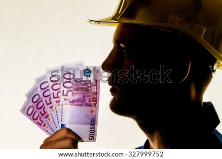 a worker in a business enterprise (craftsmen) with money bills in his hand - stock photo