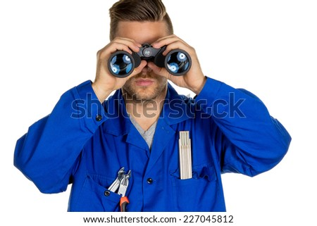 a worker in a trade or business (craftsmen) with binoculars in search of jobs or jobs - stock photo