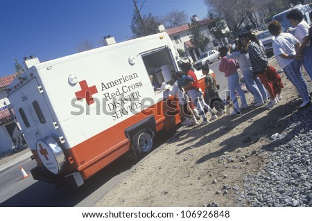 A worker in an American Red Cross Disaster Service vehicle handing out supplies to people after the 1994 earthquake