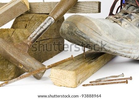A worker in safety shoes steps on a rusty nail. - stock photo