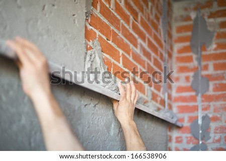A worker makes repairs the wall by level tool
