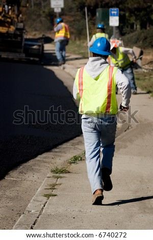 A worker on an asphalt crew running to catch up. - stock photo