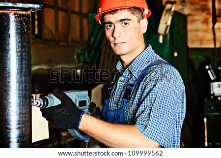 A worker with a drill at a manufacturing area. - stock photo