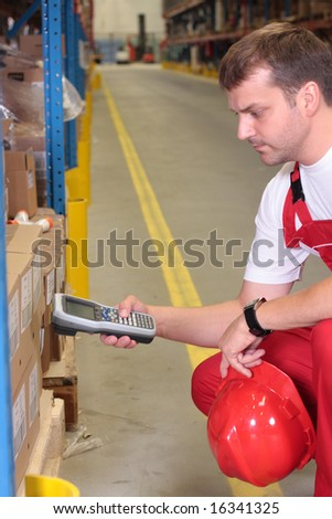 A worker with scanner in a factory maintaining stocks of finished products on the shelves in a storeroom. - stock photo