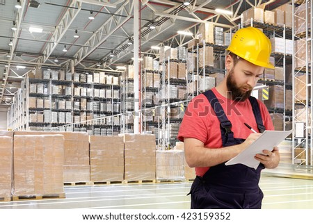 A worker writes documents in a huge distribution warehouse with high shelves