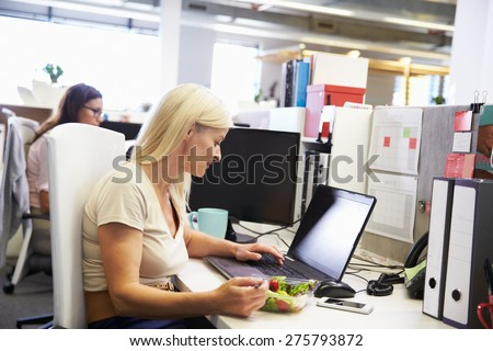 A working woman eating lunch at her desk - stock photo