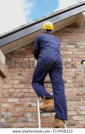 A workman climbing a ladder up to the roof - stock photo