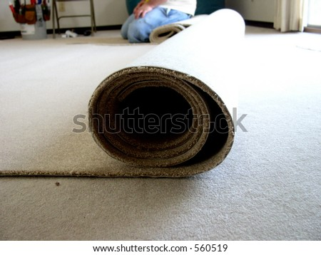 A workman in blue jeans and t-shirt kneels next to a roll of carpet ready to be cut and installed