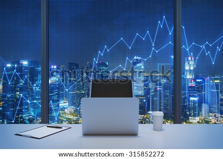 A workplace in a modern panoramic office with New York evening view and financial chart over the window. Laptop, writing pad and a cap of coffee are on the table. Office interior. 3D rendering. - stock photo