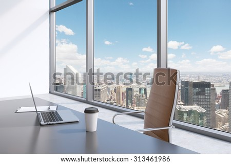 A workplace in a modern panoramic office with New York view. A grey table, brown leather chair. Laptop, writing pad for notes and a cap of coffee are on the table. Office interior. 3D rendering. - stock photo