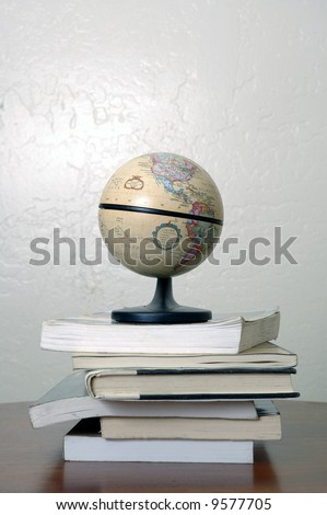 A world globe sitting on a pile of books. North and South America are visible.