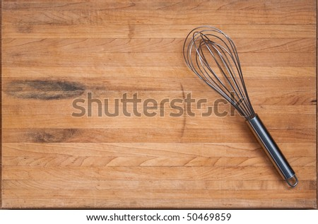 A worn butcher block cutting board sits as a background with a wire whisk to one side.