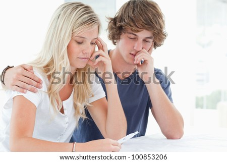 A worried couple hold each other as they look at a pregnancy test - stock photo
