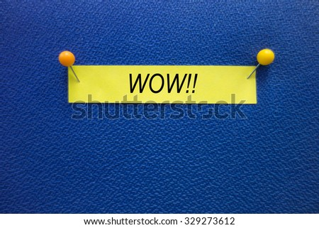 A WOW!! wording on the yellow stick note pinned on the blue board, information concept. - stock photo