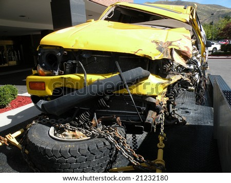 A wrecked yellow SUV strapped to a trailer