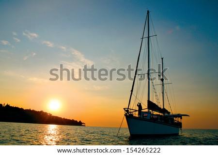 A yacht at anchor at sunrise. - stock photo