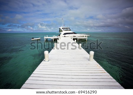 A yacht docked on Half Moon Caye Belize - stock photo