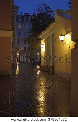 A yard with street lamps and stone pavement at evening in Saint Petersburg, Russia.