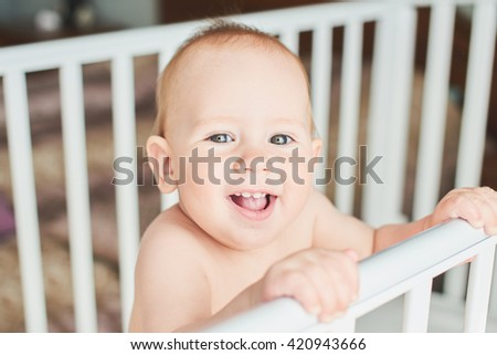 A year old baby is smiling in the crib and holds onto the side of the bed