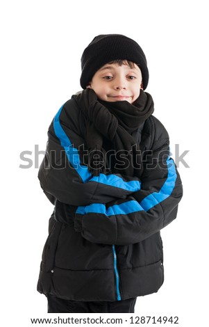 A 9 year old boy keeping warm in a winter coat isolated on a white background