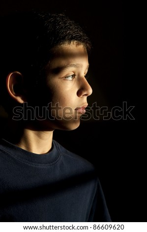 a 9 year old boy looking through the shutters in the early morning. - stock photo