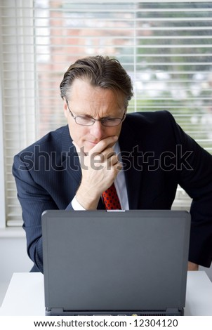 A 43 year old businessman working at his computer. - stock photo