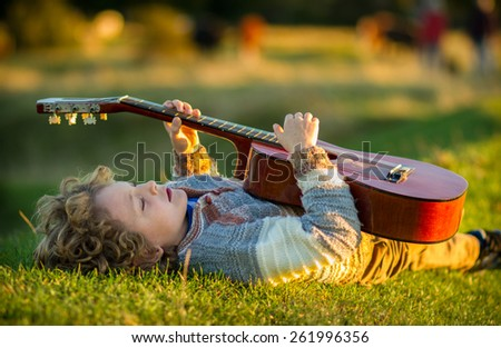 a 7 year old caucasian boy with blonde curly hair laying on his back on grass at sunset playing a guitar. there is a nice green and yellow soft focus background - stock photo