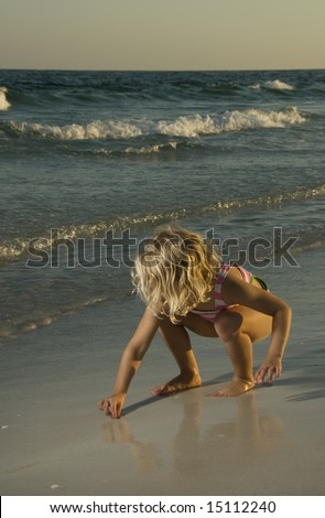 A 4 year old girl in a swimsuit discovering wonders in the beach sand at sunset.