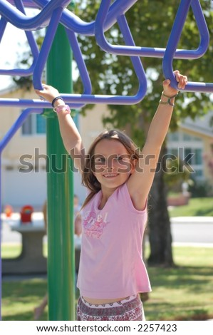A 9 year old girl playing on the monkey bars in a park. - stock photo
