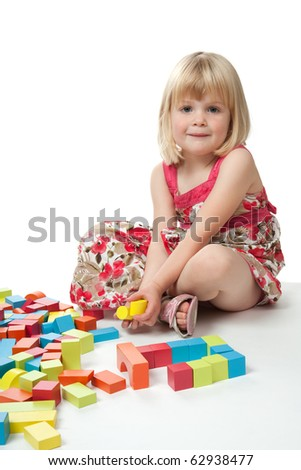 A 4 year old girl sitting and looking at camera whilst playing with some multi-coloured blocks.