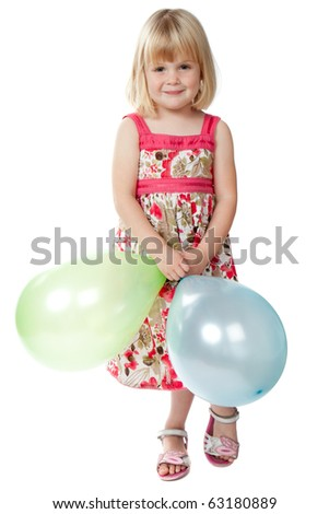 A 4 year old girl standing and looking at camera whilst playing with some multi-coloured balloons.