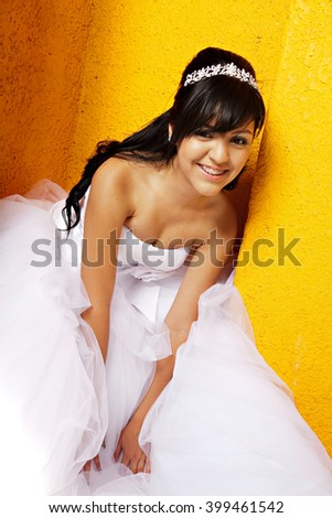 A 15 year old hispanic girl celebrates her birthday with a tiara and fancy white dress - stock photo